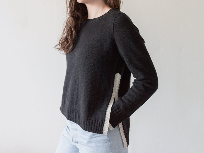 three-quarter view of woman wearing black long sleeved sweater which is longer at the back, with a split to the waist trimmed in white yarn