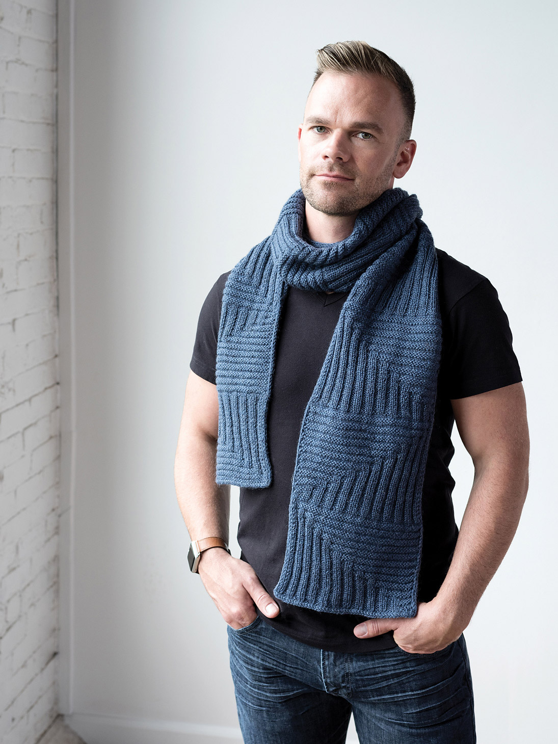 man wears a blue scarf wrapped once around his neck. Scarf is textured with blocks of horizontal and vertical stripes that meet to create diagonals