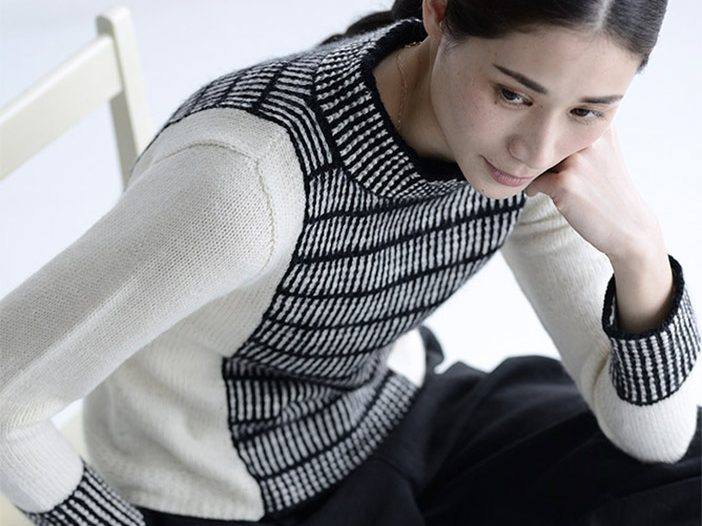 woman wearing a black-and-white sweater sits on a chair, seen from above. Sweater has central panels knit in horizontal black-and-white stripes and side panels and sleeves in white, with cuffs and a funnel neck in black-and-white textured stripes