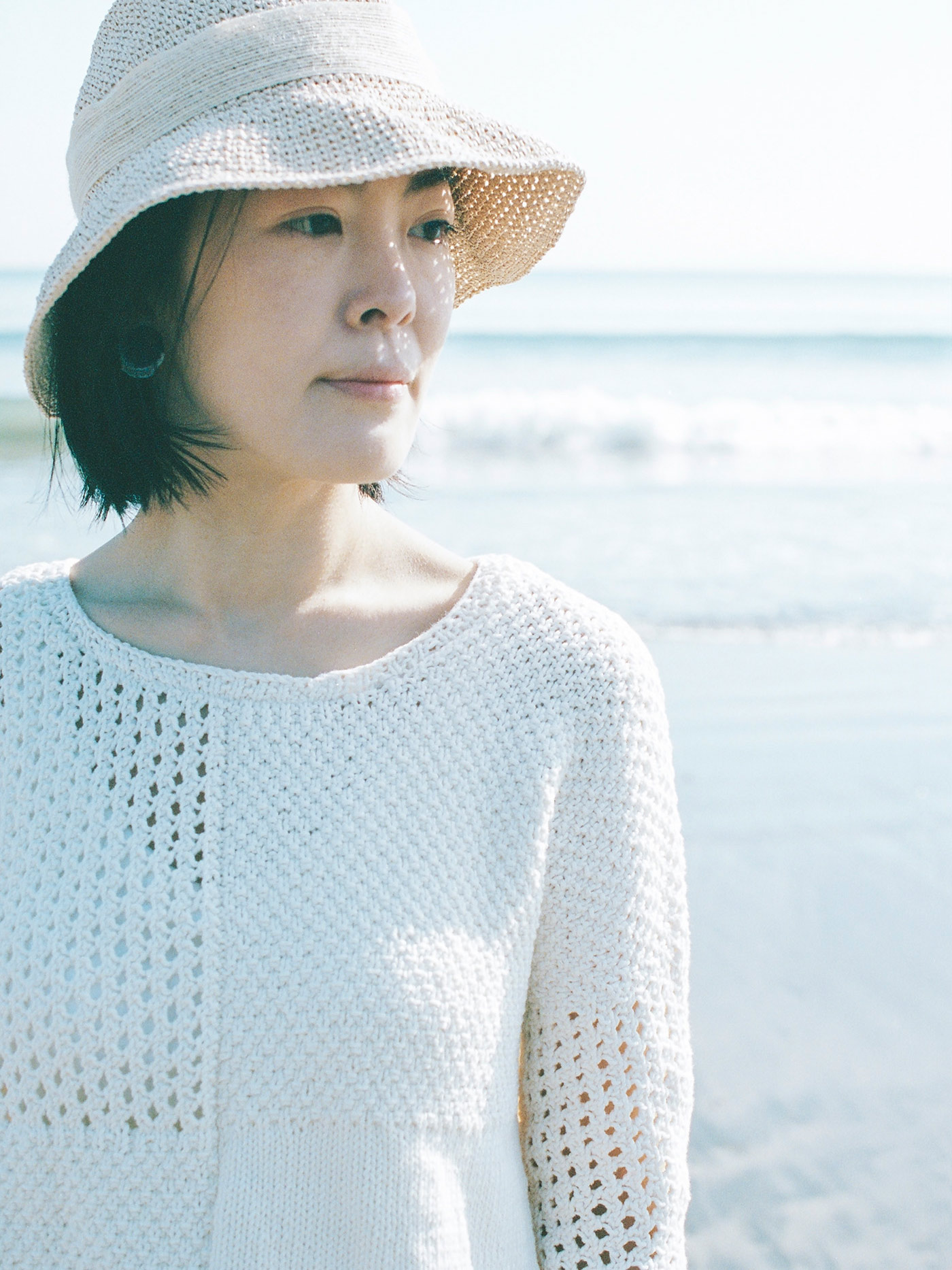 close-up view of woman standing at the ocean wearing a white drop shoulder cotton sweater. Body of sweater is divided into four quarters, one in stockinette, one in an open eyelet stitch, and two in double moss stitch. One sleeve is knit in eyelet stitch, another in double moss stitch