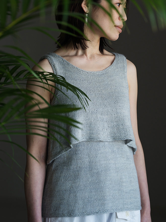 front view of woman wearing light grey knitted tank top which is made up of two layers. The base layer is plain and a-line shaped, the top layer is flared and cropped, creating a gentle flounce