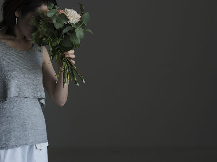 front view of woman smelling a bouquet of flowers and wearing light grey knitted tank top which is made up of two layers. The base layer is plain and a-line shaped, the top layer is flared and cropped, creating a gentle flounce