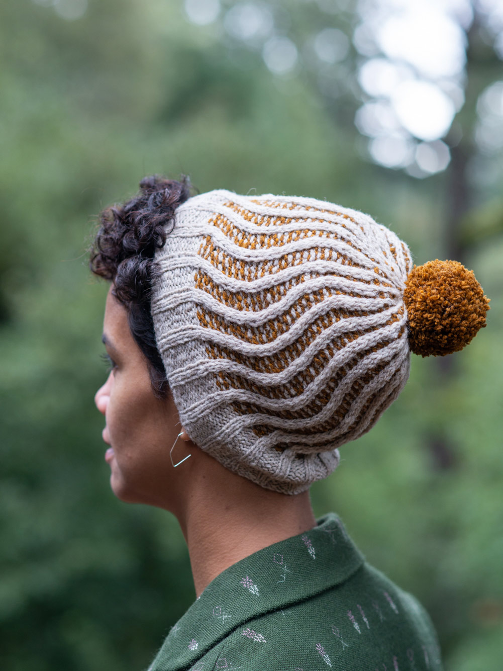 back view of woman in forest wearing a mustard yellow and off-white hat, featuring an all-over pattern of winding stitches in off-white over a background of reverse stockinette worked in 1-row stripes of alternating mustard yellow and off-white. Hat as a mustard yellow pom pom