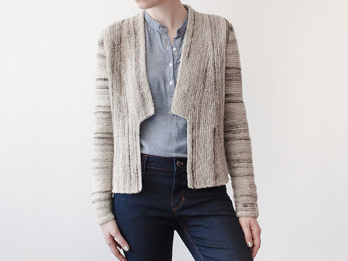 front view of woman wearing an open-front cardigan with lapels. Cardigan is worked in garter stitch in an off-white yarn streaked with dark brown, showing off the sideways construction of the body