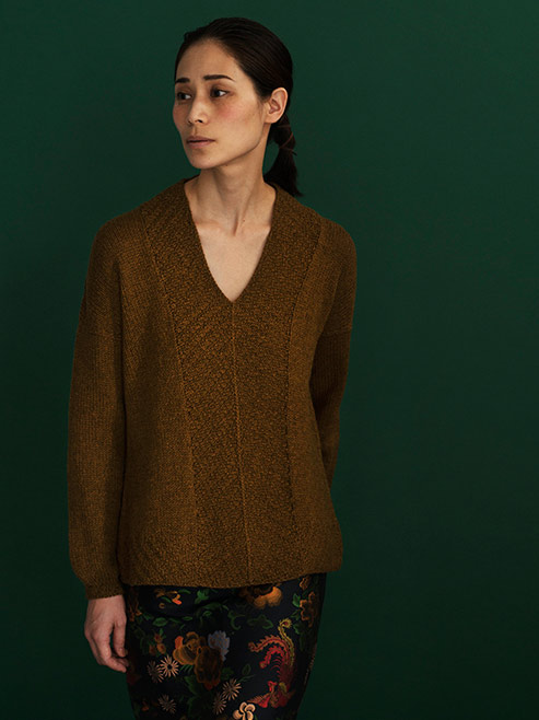 front view of woman standing in front of dark green wall, wearing a dark mustard sweater with a v-neck and long sleeves. Front of the sweater has textured panels that meet at the centre front creating an angle. Sleeves are wide and cinch gently at wrist creating a rounded shape
