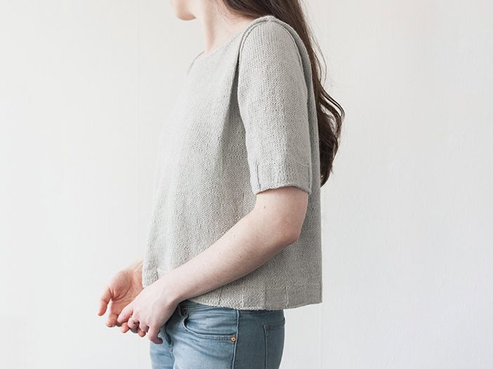 three-quarter view of woman wearing short sleeved light grey knit t-shirt with a pleated shoulder detail